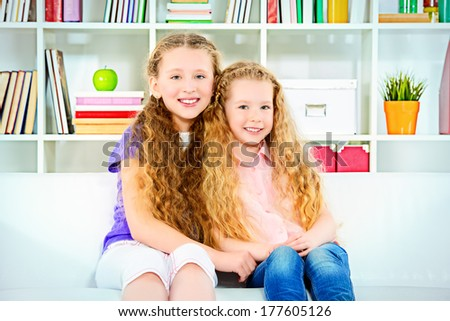 Two beautiful joyful sisters sitting on a sofa at home. - stock photo