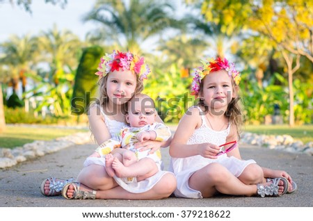 Two beautiful little blond girls with tiaras of colorful flowers on their heads, and baby sitting on the ground, hugging and smiling. Tropical vacation at the resort. - stock photo