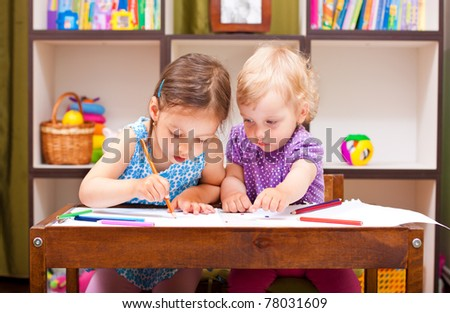 two beautiful little girl drawing near the table - stock photo
