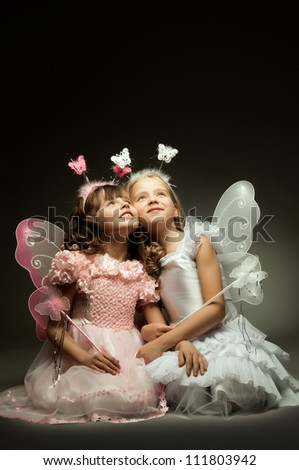 two beautiful  little girl with wings, sit and  smile on dark background - stock photo