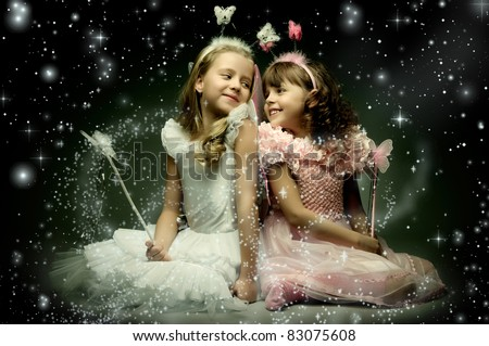 two beautiful  little girl with wings, sit and  smile on dark starry sky background - stock photo
