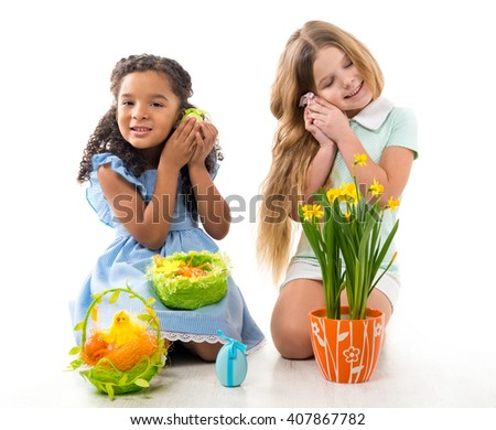 two beautiful little girls playing fluffy chicken toys on the floor isolated on white background