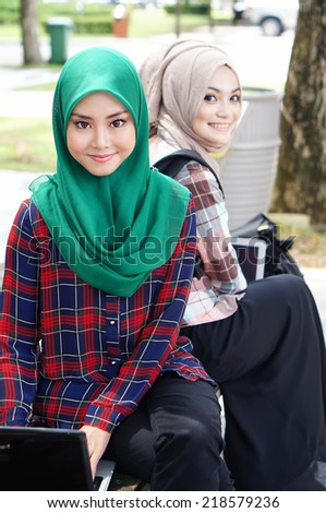 two beautiful muslim girl with laptop at he universiy park - stock photo