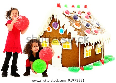 Two Beautiful Preschool African Hispanic Sisters Building Giant Gingerbread House over white background. - stock photo