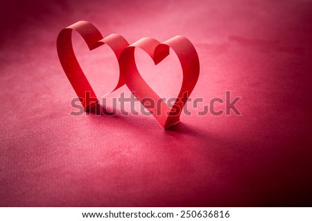 two beautiful romantic heart, made of paper tape in the shape of heart on a red paper background - pictures concept theme Love and St. Valentine's Day - stock photo