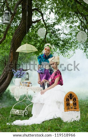 Two beautiful romantic women on a picnic in a fairy foggy  forest. Outdoors. - stock photo