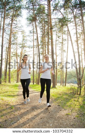 Two beautiful runnersjogging in the sunny forest - stock photo