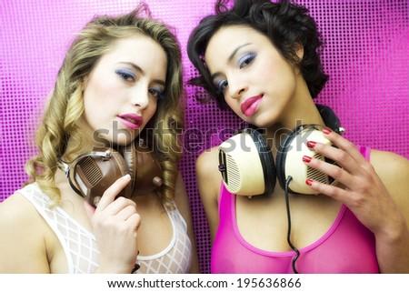 two beautiful sexy disco women in a bar lounge setting - stock photo