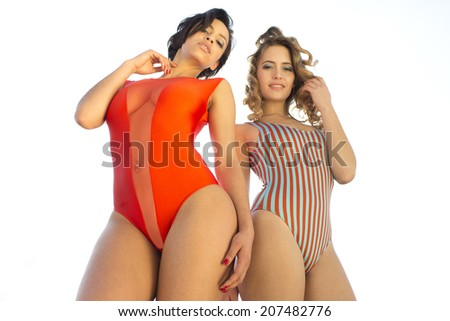 two beautiful sexy women outside in the sunshine wearing cool bikinis. Useful for fashion, beauty, music and lifestyle - stock photo