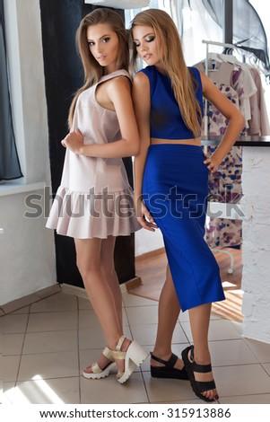 two beautiful sexy young women friends in beautiful fashion dress in the studio posing for the camera - stock photo