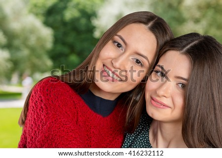 Two beautiful sisters hugging each other and smiling
