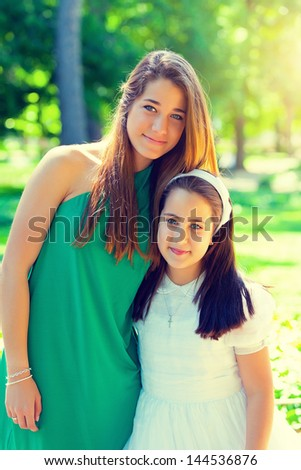 Two beautiful sisters in the First Communion Day - stock photo