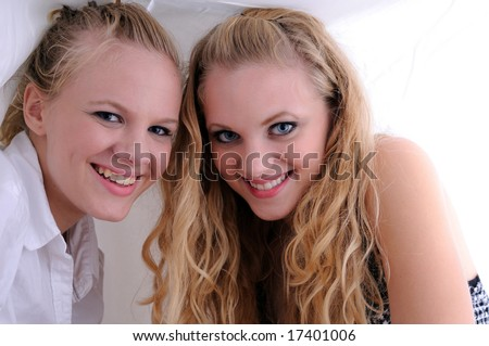 Two beautiful sisters smiling while under the covers in bed
