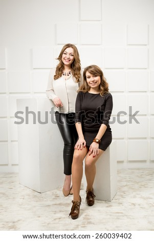 Two beautiful slim models posing in studio against white wall