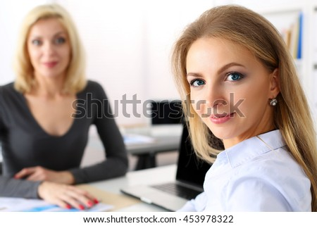 Two beautiful smiling business women at workplace in office. Discussing financial problem, loan, mortgage, investment, development, specialist communication, white collar lifestyle, job offer concept