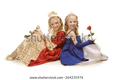 Two beautiful smiling little girls with long blonde hair in the princess costumes sitting on the floor with two roses. Red and blue empire dresses - stock photo