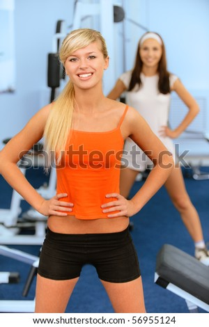Two beautiful smiling sportswomen do exercises in big sports hall.