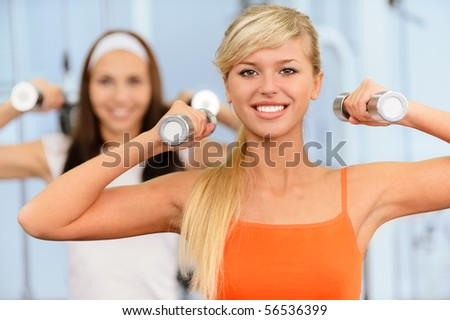 Two beautiful smiling sportswomen do exercises with dumbbells in big sports hall.