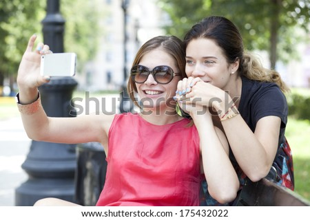 Two beautiful smiling young girl with cell phone sitting on a bench in a park