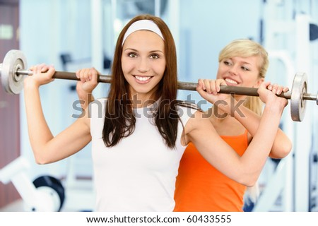 Two beautiful sportwomen make exercise on training apparatus - stock photo