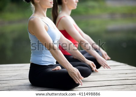 Two beautiful sporty fit young women meditating with fingers in dhyana mudra, sitting cross-legged in Half Lotus Posture, breathing, close up - stock photo