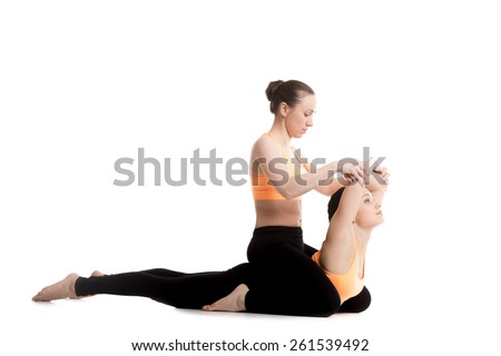 Two beautiful sporty girls in orange sportswear practice yoga with partner, instructor teaches novice student, stretching exercises for spine, Cobra posture, bhudjangasana (Bhujangasana)