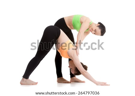 Two beautiful sporty girls practice yoga with partner, instructor assists student, stretching in downward-facing dog yoga pose, adho mukha svanasana - stock photo