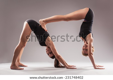 Two beautiful sporty women doing stretching exercise