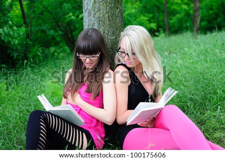 Two beautiful student girls reading books in park. - stock photo