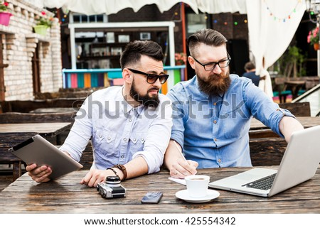 Two beautiful stylish bearded businessman with glasses in a vintage cafe negotiating, working on a laptop, next to the documents, notebook, pens, pencils, drink coffee, mobile phone - stock photo