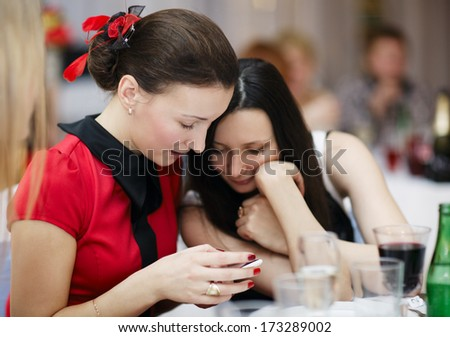 Two beautiful stylish young women at a formal event sitting together at a table reading an sms on a mobile phone - stock photo