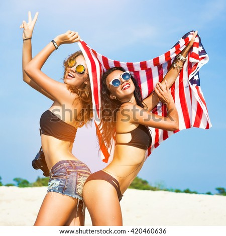 Two beautiful tanned fun hipster girls on the beach, blonde and brunette holding an American flag, old style, laugh, relax on a tropical island, sexy bikini, denim shorts, fashion sunglasses, square - stock photo