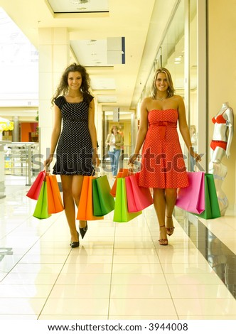 Two, beautiful woman holding bags and walking down corridor in big shop. Looking at camera - stock photo