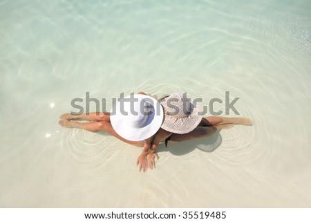 Two beautiful Woman lying in blue pool - stock photo