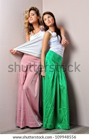 Two beautiful woman posing in a fancy dresses. Sudoi shooting. - stock photo