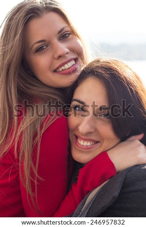 Two beautiful woman together enjoying the sunny autumn day, in the park  - stock photo