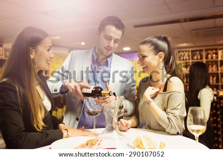 Two beautiful women and a waiter in a wine bar - stock photo