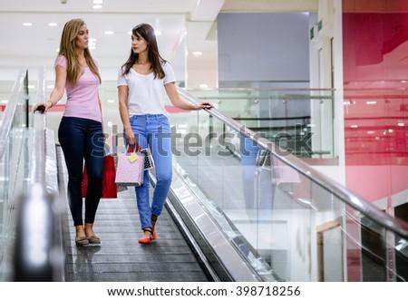 Two beautiful women carrying shopping bags on escalator of shopping mall - stock photo