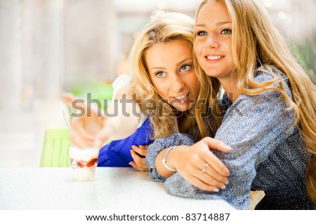 Two beautiful women drinking coffee and chatting at mall cafe. One of them pointing to copyspace and they both looking there. - stock photo