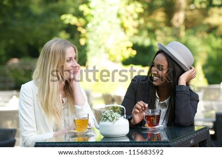 Two beautiful women drinking tea outdoors - stock photo