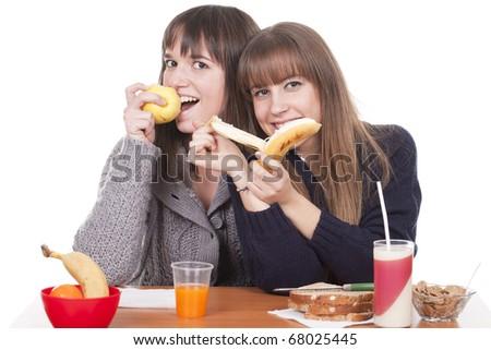 two beautiful women eating breakfast - stock photo