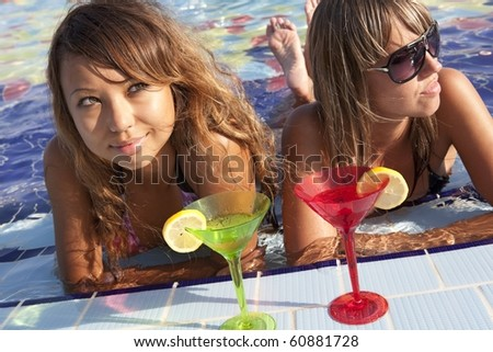 Two beautiful  women enjoying their summer vacation with a glasses of martini - stock photo