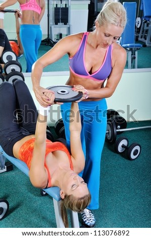 Two beautiful women exercising in gym with weights