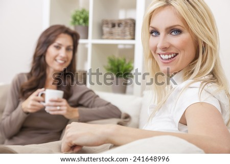 Two beautiful women friends at home drinking tea or coffee together