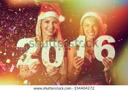 Two beautiful women having fun at New Year's Eve party, holding cardboard numbers 2016 - stock photo