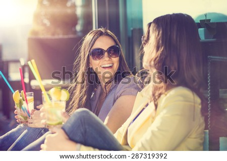 Two beautiful women having fun in a bar - stock photo