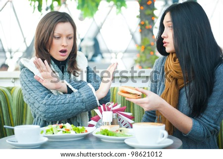 Two beautiful women having lunch and chatting at cafe. One of them saying stop to one more sandwich