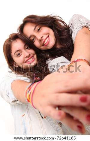 Two beautiful women holding hands in signal of  friendship - stock photo