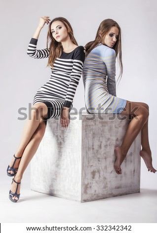 Two beautiful women in dresses on a white cube in the Studio. Models in fashionable clothes of different colors on a light background - stock photo