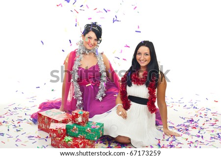 Two beautiful women in elegant dresses sitting on floor with pChristmas presents while confetti falling over them